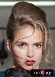 Společenský účes z vyčesaných polodlouhých vlasů hnědé barvy s blond melírem, s volně spuštěnými prameny podél tváře