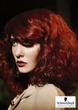 Silně zvlněný účes z dlouhých vlasů červené barvy, s ofinou na straně
