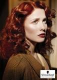 Účes z dlouhých zvlněných vlasů červené barvy, ve stylu retro, s pěšinkou na straně
