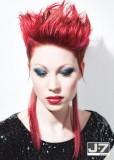 Extravagantní krátký účes s dlouhými prameny na krk, červené barvy, stylizovaný vzhůru