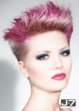 Lehce extravagantní účes z krátkých rovných vlasů blond barvy s růžovým melírem, stylizovaný vzhůru
