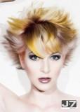 Krátký rozcuch ve stylu punk, s ofinou na straně, blond barvy se žlutým a hnědým melírem