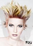 Divoký rozcuch z krátkých rovných blond vlasů se žlutým a hnědým melírem, stylizovaný vzhůru