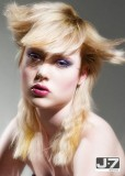 Extravagantní styling dlouhého sestříhaného účesu blond barvy, s ofinou do čela mírně na stranu