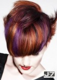 Krátký sestříhaný účes z rovných vlasů, po stranách rozcuchaný, s rovnou ofinou do čela, hnědé barvy s barevnými melíry
