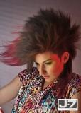 Polodlouhý účes ve stylu punk, stylizovaný vzhůru, ze skreplých vlasů hnědé barvy s červeným melírem v konečcích