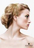 Společenský účes z blond vlnitých vlasů ozdobený zlatou čelenkou