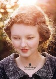 Romantický jednoduchý účes ze spletených copánku omotyných kolem obličeje, světlehnědé barvy