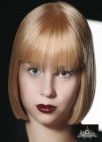 Ostře střižené mikádo z polodlouhých rovných vlasů blond barvy s rovnou ofinou do čela