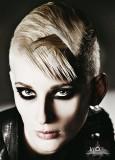 Ultra krátký účes s delší partií na temeni, nagelovanou vzhůru, blond barvy