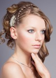 Složitě vyčesaný společenský účes z dlouhých jemně zvlněných vlasů blond barvy