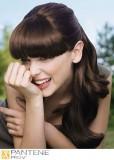 Dlouhý romantický společenský účes s rovnou hustou ofinou,  horní vlasy sepnuté, tmavohnědé barvy