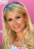 Paris Hilton - Dlouhý zvlněný účes blond barvy s ofinou na straně a zdobený čelenkou