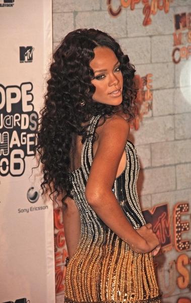 Rihanna - Účes z dlouhých hodně zvlněných vlasů hnědé barvy s pěšinou uprostřed