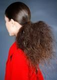 Extravagantní culík s vlasy u hlavy uhlazenými a v culíku bohatě natupírovanými, tmavohnědé barvy