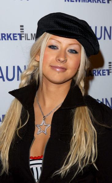 Christina Aguilera - Blond účes z volně spletených copů doplněný o trendy čepici
