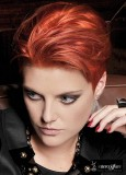 Krátký sestříhaný účes stylizovaný dozadu, červené barvy