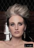 Účes z dlouhých vlasů tmavohnědé barvy vyčesaný do culíku, na temeni tupírovaný a blond barvy