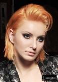 Rovné hladké mikádo z rovných vlasů oranžové barvy se zvlněnou ofinou