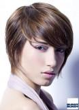 Elegantní účes z rovných krátkých vlasů hnědé barvy s ofinou stylizovanou dopředu do čela