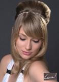 Vyčesané vlasy na temeni, vepředu se spuštěnými prameny podél obličeje, doplněné tenkou čelenkou