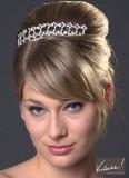 Účes z vyčesaných natupírovaných vlasů, rovnou ofinou na bok, ozdobený stříbrnou sponou