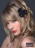 Účes z romanticky natočených blond vlasů, na boku s ozdobou ve tvaru růže