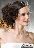 Od temene uhlazené vlasy stylizované na bok a hustě natočené do pevných vlnek