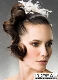 Vlasy vyčesané do drdolu s pramenem stočeným do tváře, s doplňkem bílého peří