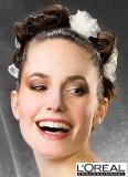 Vyčesaný účes z dlouhých vlasů, s důrazem na doplněk velké bílé kytky