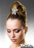 Něžný účes z vyčesaných vlasů do objemného drdolu, se stříbrnou vlasovou broží