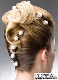 Uhlazené vlasy vyčesané na temeni s elegantními vlnami, ozdobené perlami
