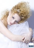 Žensky kudrnaté vlasy stylizované na temeni dovrchu, vhodné na svatbu