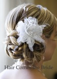 Noblesní svatební účes s květinou na vlasech seplých do drdolu  v týle