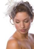 Účes na svatbu s pavučinovým závojem a květinou na vyčesaném drdolu