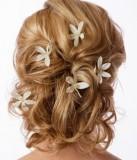 Svatební vzhled víly, doplněný květinami v polodlouhých zvlněných vlasech