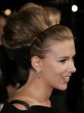 Scarlett Johansson - Extravagantní účes ze štědře natupírovaných vlasů do drdolu, ozdobené květinou
