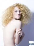 Bohatý účes z kudrlin na dlouhých blond vlasech