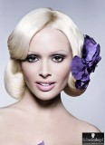 Krásná neznámá s fialovou květinou v sepnutých vlasech
