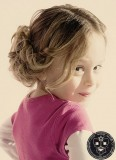 Dívčí lokny v drdolu s uvolněným pramenem
