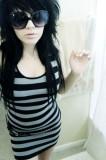 Emo účes sestříhaný, z dlouhých černách vlasů, účes doplněný o velké brýle