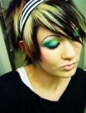 Krátký emo účes černé barvy s blond partií na temeni hlavy, s červeným melírem