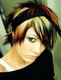 Dámský emo účes z krátkých vlasů blond barvy podbarvený černě, s červeným melírem