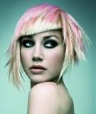 Netradičně střižený blond účes do podkovy s šikmou ofinou a růžovým melírem
