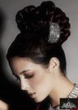 Společenský vyčesaný účes z dlouhých hnědých vlasů dozdobený sponou