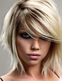 Dámský polodlouhý blond účes s hnědým melírem, s ofinou na straně přes oko, postupně sestříhaný ve spodních partiích