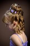 Složitý účes zdobený fialovými kvítky