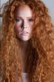 Kudrnatý sexy účes z měděných vlasů