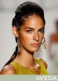 Letní  účes z dlouhých vlasů svázaných v copu, s ofinou stylizovanou dozadu, hnědé barvy