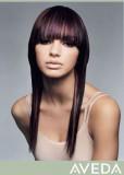 Účes z dlouhých postupně sestříhaných vlasů fialové barvy, s hustou rovnou ofinou do čela